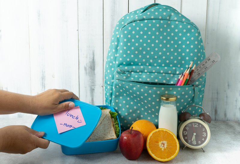 a backpack and lunchbox with various fruits and milk